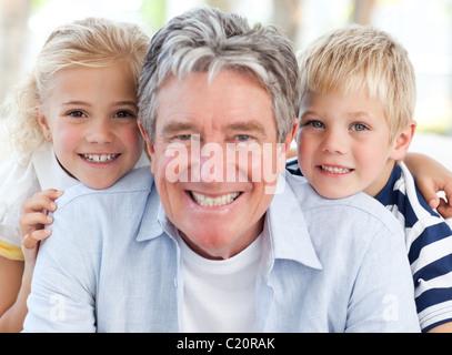 Joyfull piccolo famiglia guardando la telecamera Foto Stock