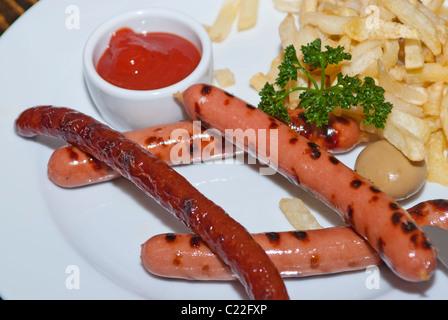 Salsicce alla griglia con patatine e salsa di pomodoro Foto Stock
