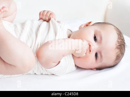 Ritratto di un simpatico neonato sdraiato sul divano nella sua camera da letto Foto Stock