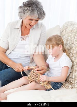 Nonna aiutare la sua bambina a lavorare a maglia Foto Stock