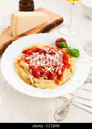 Una piastra di penne la pasta con la salsa di pomodoro e formaggio parmigiano grattugiato Foto Stock