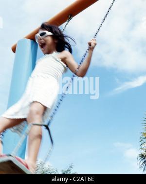 Ragazza che gioca su swing, basso angolo di visione Foto Stock