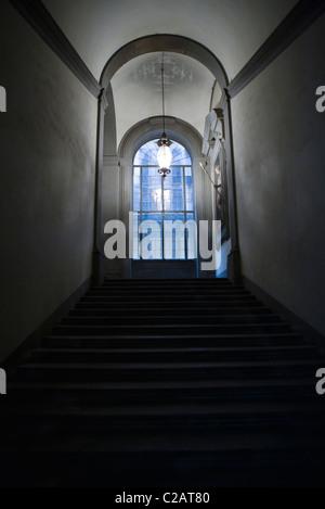 La tromba delle scale che conducono alla finestra vetrata, lampada pendenti dal soffitto Foto Stock