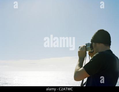Uomo di fotografare vista oceano con la fotocamera Foto Stock
