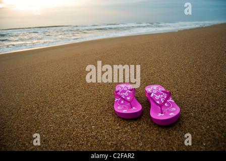 Rosa donna flip-flop su un vuoto e pulita spiaggia di sunrise. Foto Stock