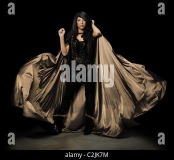 Vampiro femmina con mantello su sfondo scuro Foto Stock