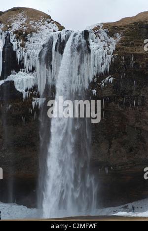 Seljalandsfoss cascata nella neve, con acqua congelata come ghiaccio, Sud dell'Islanda Foto Stock