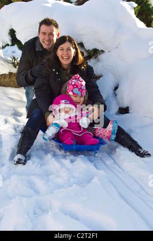 Ritratto verticale di una giovane famiglia, mamma, papà e due ragazze giovani tutti insieme giocando su una slitta Foto Stock