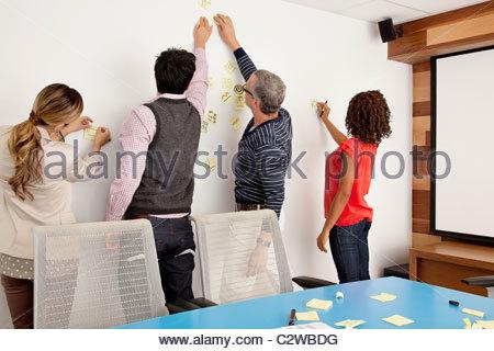 La gente di affari mettendo note adesive sulla conferenza di parete della camera Foto Stock