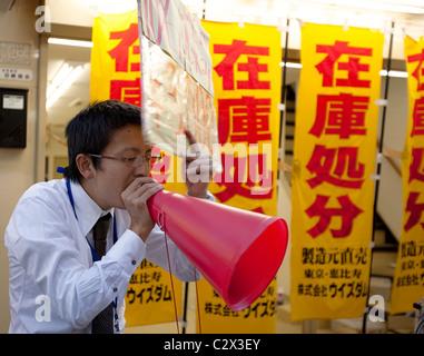 Un uomo con un rosso megafono in plastica su una strada del mercato DI TOKYO GIAPPONE WITHE banner colorati sullo Foto Stock