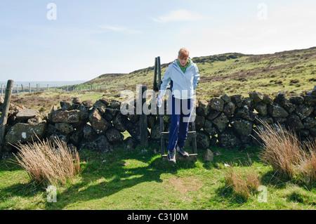 La donna si arrampica su un montante verticale su una pietra a secco in parete le colline di Antrim Foto Stock