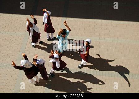 Oman, Moscato, vista dall'alto di scuola le ragazze a giocare con le braccia sul terreno in una giornata di sole Foto Stock