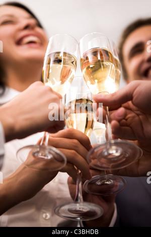 Close-up di mani umane che allietava con flauti di golden champagne Foto Stock