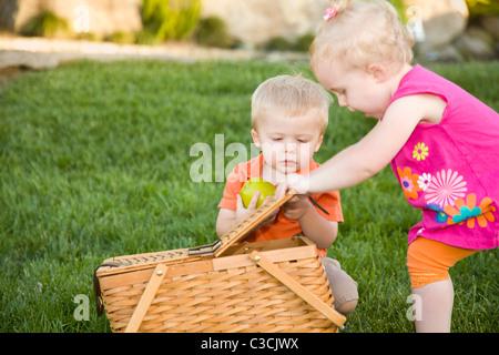 Carino Twin fratello e sorella e i bimbi a giocare con Apple e Cesto picnic nel parco. Foto Stock