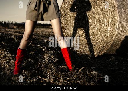 Ragazza in rosso gli stivali da pioggia nel campo Foto Stock