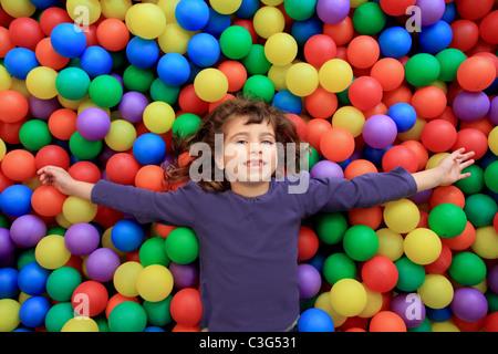 Coloratissime palle funny park bambina giacente gesticolando felice Foto Stock