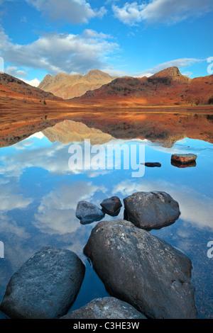 Il tardo autunno linee di ghiaccio le sponde rocciose di Blea Tarn nella parte anteriore di un perfetto riflesso Foto Stock