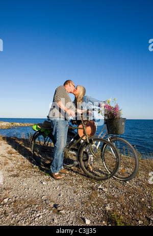 Coppia matura equitazione bicicletta sulla spiaggia e baciare Foto Stock