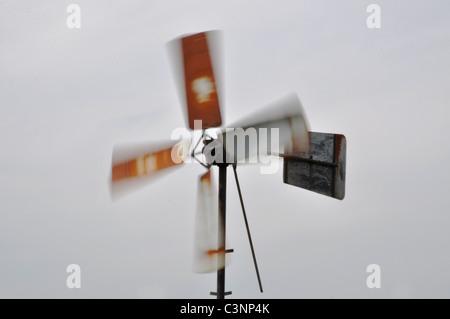 Rusty windmill girando follemente nel vento Foto Stock