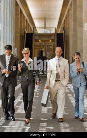 La gente di affari a piedi lungo un corridoio Foto Stock