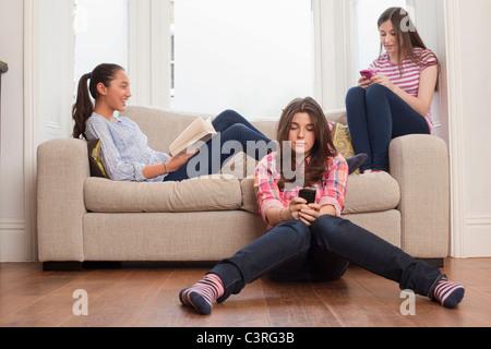 Le ragazze adolescenti seduti sul divano lettura , la verifica dei messaggi Foto Stock