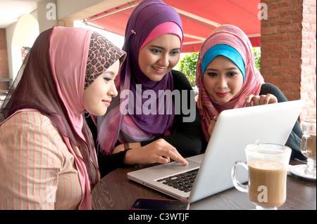 Piuttosto giovane donna musulmana in sciarpa avente la discussione utilizzando laptop in cafe con gli amici Foto Stock