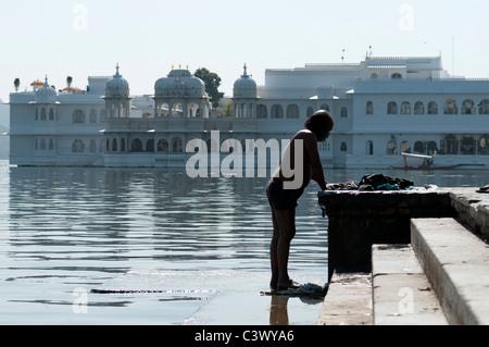 L'uomo lavare le vesti di fronte al palazzo di Udaipur. Foto Stock