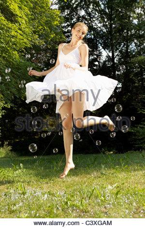 Giovane donna felice in abito bianco jumping in midair con bolle all'aperto Foto Stock
