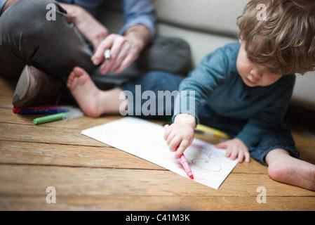 Il Toddler ragazzo seduto sul pavimento con un genitore, disegno su carta Foto Stock