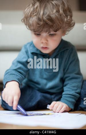 Il Toddler ragazzo seduto sul pavimento, disegno su carta Foto Stock
