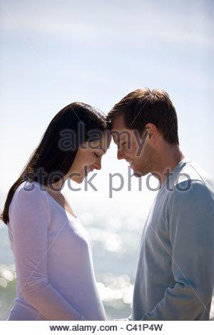 Una donna incinta e il suo partner sulla spiaggia, teste di toccare Foto Stock