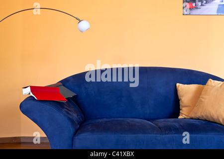 Un angolo lettura con un lettino blu un libro e una lampada da