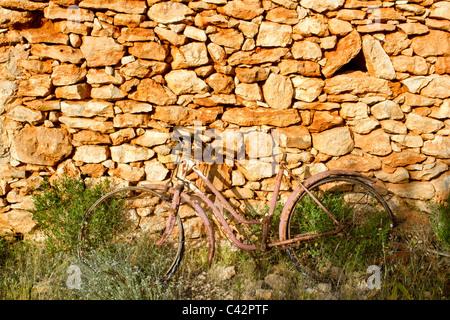Bicicletta invecchiato arrugginito sul muro di pietra romantica malinconia ricordi Foto Stock