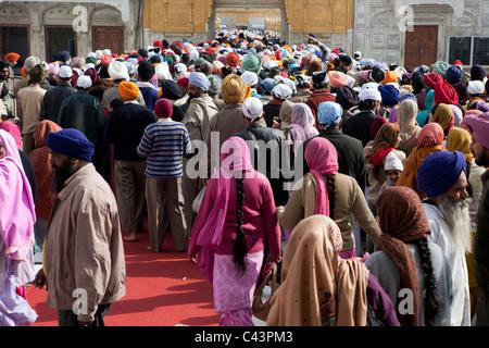 Persone di andare a principale tempio dorato al gate, Tempio Dorato, Amritsar Punjab, India Foto Stock