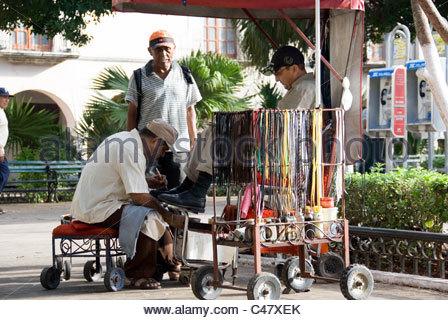 Recuperando la mattina Gossip oltre a pulire e lucidare al Lustrascarpe stallo, Zocalo piazza cittadina, Merida, Foto Stock