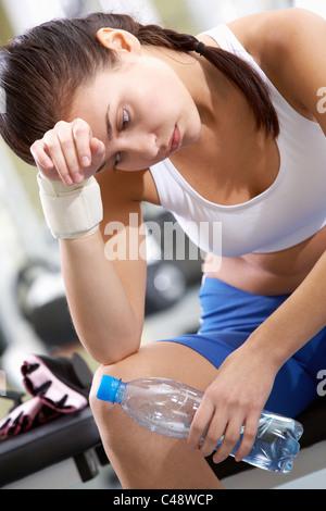 Ritratto di stanchi brunette con bottiglia di acqua in mano avente il resto dopo allenamento Foto Stock