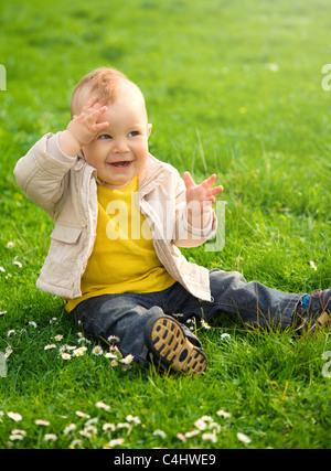 Little Boy è seduta sul prato verde che copre la sua gli occhi dal sole Foto Stock