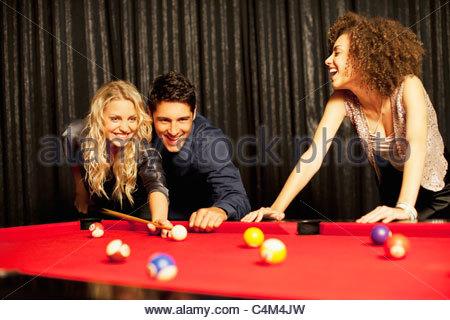 Amici giocando a biliardo Foto Stock