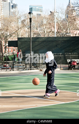 Piuttosto giovane ragazzina musulmana in testa con sciarpa abaya nero sui suoi jeans gioca con la palla calcio in Foto Stock