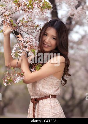 Ritratto di una giovane e bella sorridente donna asiatica sta in piedi in una fioritura di ciliegio in un parco Foto Stock