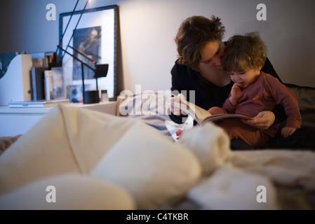 Azienda madre figlio toddler sul giro, lettura Bedtime Story nel letto Foto Stock