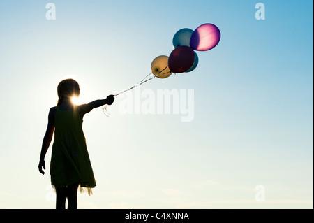 Silhouette di una ragazza giovane azienda di palloncini colorati al tramonto Foto Stock