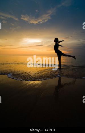 Una giovane donna facendo esercizi yoga sulla spiaggia al tramonto.Preso in Phra Ae Beach (Long Beach), Koh Lanta Foto Stock