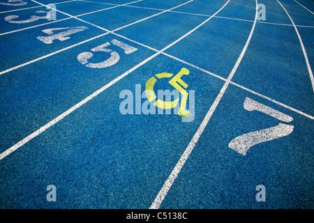 Handicap icona sedia a rotelle sovrapposti sulla sommità della via di corsa. Foto Stock