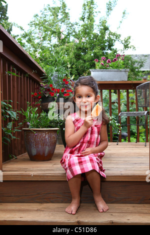 Bambina in rosa plaid dress seduta sul ponte posteriore di mangiare un ghiaccioli dessert congelato. Foto Stock