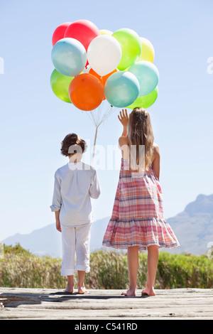 Vista posteriore dei fratelli giocando con palloncini a un molo Foto Stock