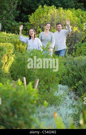 Coppia matura a piedi con la loro madre e agitando la mano in un giardino Foto Stock