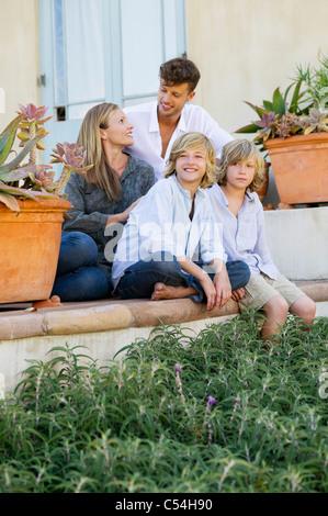 Famiglia seduti insieme al di fuori della loro casa Foto Stock
