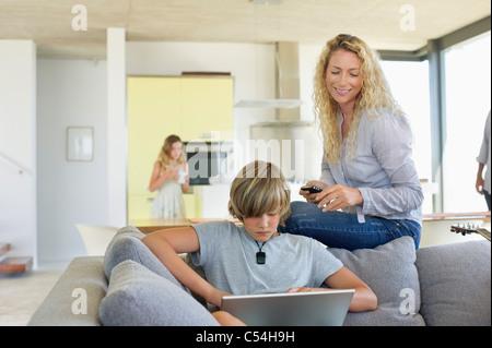 Ragazzo adolescente usando un computer portatile e di sua madre guardando lui Foto Stock