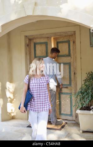 Donna che cammina con l uomo a bloccare lo sportello in background Foto Stock